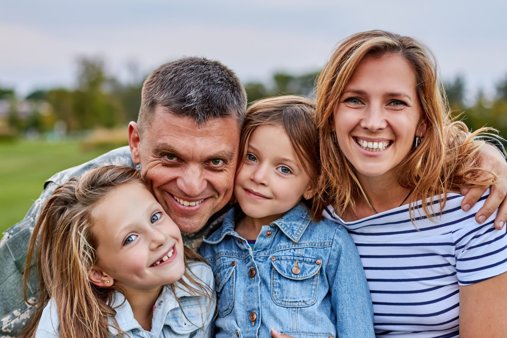Portrait of happy family. Shot of smiling cheerful mature soldier with his family outdoor.